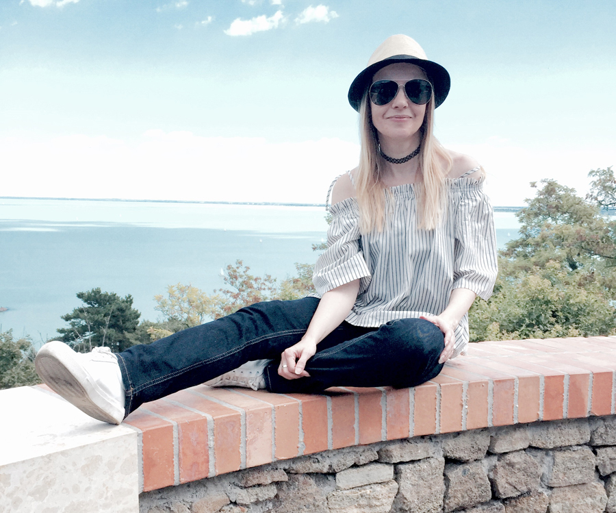 off-shoulder striped top, indigo slim straight jeans, white trainers, straw trilby, Nineties nylon choker, aviators, Balaton view